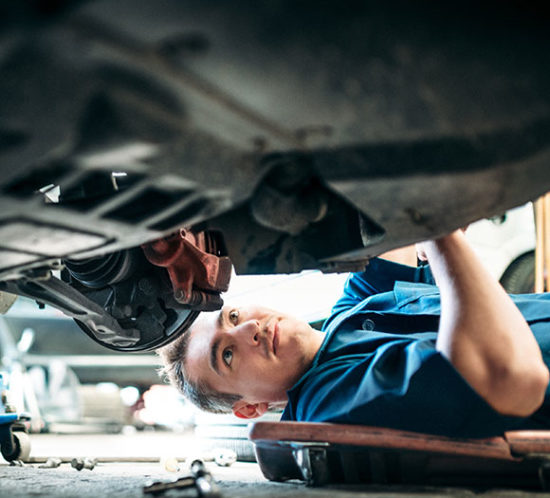 Motor Trade Worker repairing underside of a car to promote Powell Commercial Insurance Brokers - Motor Trade Insurance